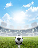 Stadium Soccer Pitch And Ball. A soccer stadium with a marked green grass pitch and a soccer ball in the center in the daytime under a blue sky Stock Photos