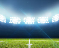 Stadium And Soccer Pitch. A soccer stadium with a marked green grass pitch at night under illuminated floodlights Stock Photos