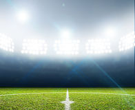 Stadium And Soccer Pitch. A soccer stadium with a marked green grass pitch at night under illuminated floodlights Stock Photo
