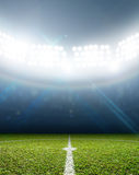 Stadium And Soccer Pitch. A soccer stadium with a marked green grass pitch at night under illuminated floodlights Royalty Free Stock Images