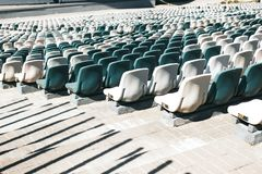 Stadium stands with aisles and white and gray plastic seats stock image