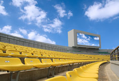 Stadium under the sky. Yellow seats and electronic billboard display at stadium royalty free stock images