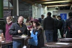 Stadmarknadsrestaurang med folk som äter på tabeller utanför på trottoar arkivbilder