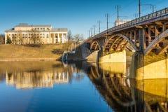 Stads- arkitektur, en bro i retro stil med välvda spännvidder och massiv gul service reflekteras i den blåa floden Royaltyfri Bild