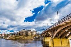 Stads- arkitektur, en bro i retro stil med välvda spännvidder och massiv gul service reflekteras i den blåa floden Arkivbild