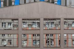 stads- arkitektur Förvriden reflexion av en byggnad i spegelförsedda fönster av annan Royaltyfri Fotografi