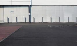 stads- bakgrund En genomskärning av gator framme av en modern vit byggnad med en rad av metallgatapoler royaltyfria foton