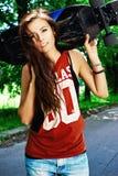 Stads- flicka med longboard Arkivfoto