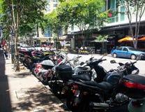 Stads- gata med motorcyklar som parkeras längs en sida och för hyracyklar och bilar på annan i Brisbane Queensland Australien N royaltyfri foto