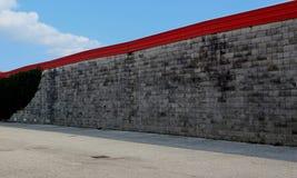Stads- gatabakgrund Asfaltväg tillsammans med en vägg som överst göras av små konkreta kvarter med den röda kanten royaltyfri fotografi