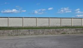 Stads- gatabakgrund En asfaltväg framme av en lång konkret tegelstenvägg under en blå himmel med fluffiga moln royaltyfri fotografi