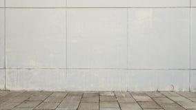 Stads- gatabakgrund Vit vägg och grå färger belagt med tegel golv Arkivfoton