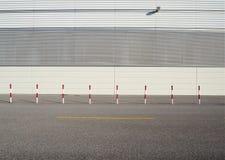 Stads- gatabakgrund Vita och röda vägrenpoler på asfaltvägen framme av en vit vägg som göras av aluminium paneler royaltyfri foto
