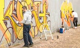 Stads- gatakonstnärer som målar färgrika grafitti på den generiska väggen Royaltyfri Bild