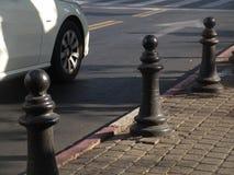Stads- gatasikt av en vit bilkörning på vägen med en diagonal sammansättning och sikt av trottoaren i dagsljus arkivfoto