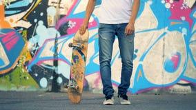 Stads- grafittivägg med en ung man som lyfter hans skateboard förbi ett bentrick arkivfilmer