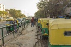 Stads- indier för gata som parkerar gröna gula rickshaws nära trottoaren med folk royaltyfri foto