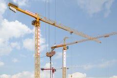 Stads- industriellt landskap med tre tornkranar Arkivbild