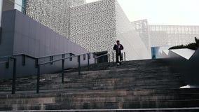 Stads- jogger på trappuppgången Idrottsman nen ner trappan Mannen kör upp trappan lager videofilmer