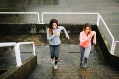 Stads- konditionkvinnor som kör och klättrar trappa Fotografering för Bildbyråer