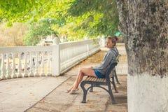 Stads- kvinnasammanträde på en bänk av en djup ny luft för parkera och för andning Royaltyfri Foto