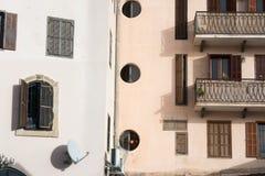 Stads- stads- landskap för abstrakt stads- grungebakgrund: kombination av väggar av två hus med trätappningfönster och balconi Royaltyfria Foton