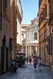Stads- plats med en gammal kyrka på en smal gata i Rome Arkivbild