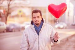 Stads- romans: stående av ett le stiligt skäggigt mananseende i en stadsgata med luftballongen som formas som röd hjärta tonat royaltyfria foton