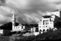 Stads- sikt för middagar av en kyrka och ett intressant arkitekturhus med fyra golv, balkonger och bågar, under en molnig himmel, royaltyfri bild