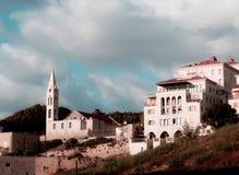 Stads- sikt för middagar av en kyrka och ett intressant arkitekturhus med fyra golv, balkonger och bågar, under en molnig himmel arkivfoton