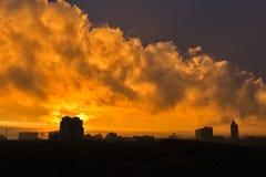 Stads- solnedgånghorisont med dramatiska orange moln Arkivfoto