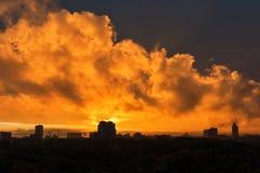 Stads- solnedgånghorisont med dramatiska orange moln Royaltyfri Foto