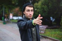 Stads- stående av denseende unga mannen som bär det stilfulla omslaget som framme ser av honom och pekar pekfingret arkivfoto
