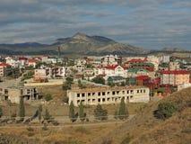 Stads- stad för landskap bland bästa sikt för berg Arkivbild