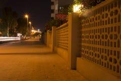 Stads- stadsgata med billjusslingor och dekorerat staket på N arkivbilder