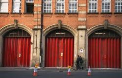 Stads- symmetri i London Folk som förbigår en industribyggnad med stora röda dörrar Royaltyfri Bild