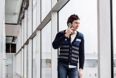 Stads- talande telefon för affärsman nära ett fönster Arkivfoto