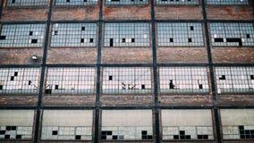 Stads- tegelstenbyggnad med brutna fönster Arkivfoto