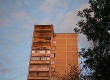 Stads- tegelstenbyggnad med trådar i solnedgången fotografering för bildbyråer