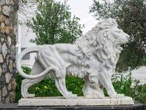 Stadsbeeldhouwwerk van een witte leeuw met open mond bij de ingang Lokaal oriëntatiepunt stock foto's