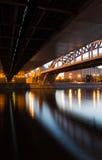 Stadsbro över floden på natten royaltyfri bild