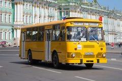 Stadsbuss LiAZ-667 på bakgrunden av vinterslotten Den tredje ettåriga växten ståtar av retro transport i St Petersburg Arkivbild