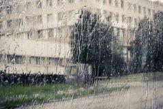 Stadsbyggnaden bak fönstret som fylls in med rommar arkivbild