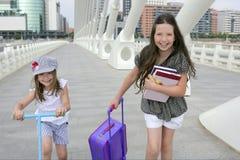 stadsflickor som går little skoladeltagare till Arkivfoton