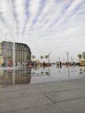 Stadsfyrkant med springbrunnar under molnig himmel Arkivfoto