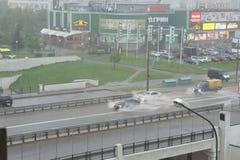 Stadsgata efter en hällregn och bilar som är rörande på den royaltyfria bilder