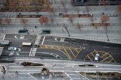 Stadsgata med asfaltvägen och vit- och gulingmarkeringslinjer och pilar och tecken Arkivfoton