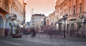 Stadsgatan med shoppar, byggnader och folk arkivfoto
