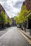 Stadsgatasikt med nya gröna träd, tidig vår royaltyfria bilder