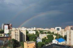 Stadsgebouwen op de achtergrond van zwarte hemel met regenboog stock foto's